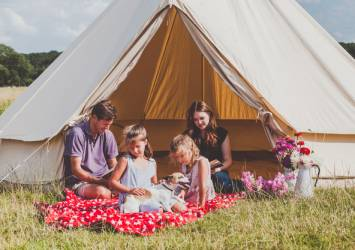 Family by tent with Snuggle Sac blanket